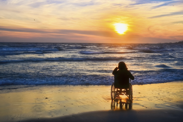 Sunset, makes sightseeing on the beach a woman on a wheelchair
